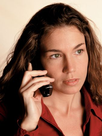 A beautiful and serious business woman on a portable phone.