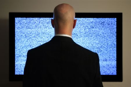 A man watching a blank or static screen of his television.