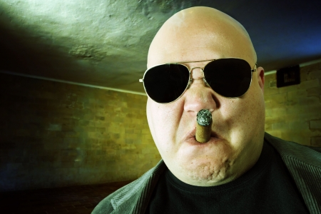 Image of a mobster, gangster, or boss in a dark factory setting. Harsh lighting, high-contrast and cross-processing for meaner look.