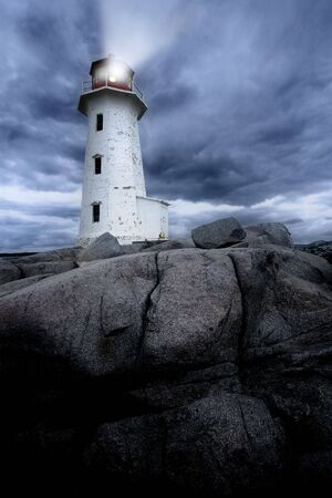 The lighthouse at Peggy's Cove in Nova Scotia Canada at dusk as a storm grows.