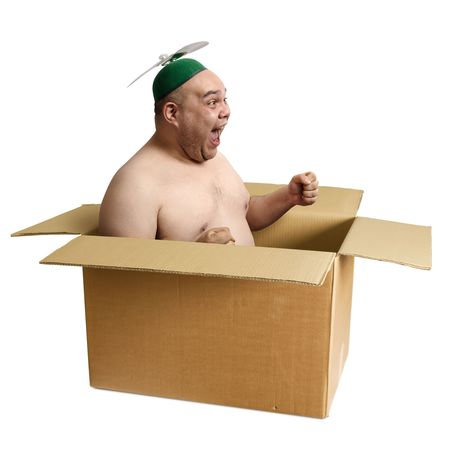 An adult male in his 30's playing airplane in an old cardboard box.