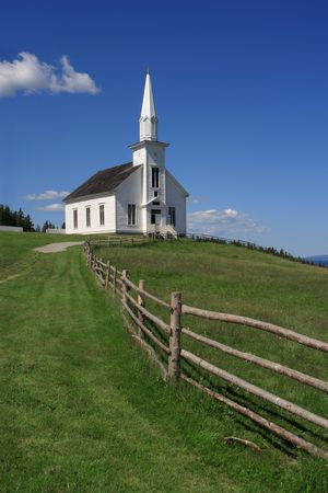 Photo of a little white wooden church in the countryside.