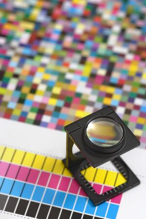 Shallow depth of field image of a printers loupe on printed sheet.  Focus is on the top of the loupe.