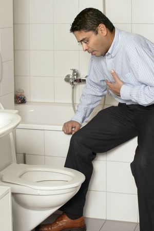 Photo of an adult male in his late thirties with stomach sickness about to vomit into his toilet.