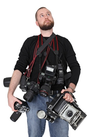 Photo of a man in his late twenties, standing and holding many cameras, film, digital, medium format and large format.