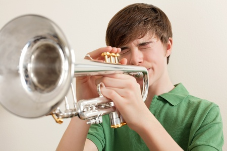 Photo of a young teen playing his silver trumpet.