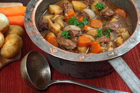 Photo of of Irish Stew or Guinness Stew made in an old well worn copper pot.