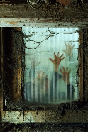 Photo of zombies outside a window that is covered with spiderwebs and filth.