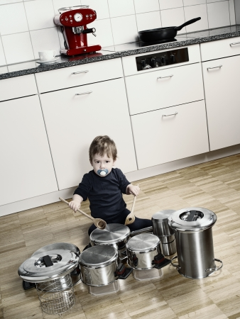 an adorable young boy using wooden spoons to bang pots and pans that are set up like a drum set. Desaturated and contrast increased.