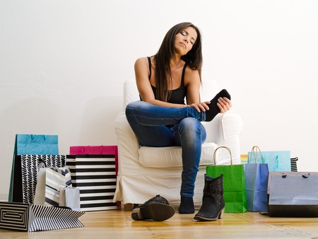 Photo of a young beautiful female sitting on a chair surrounded by shopping bags and rubbing her sore feet.