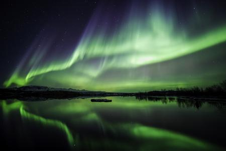 Foto de Northern lights blazing over lake Thingvellir national park in Iceland - Imagen libre de derechos