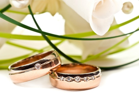 Pair of golden wedding rings with rose bouquet. Macro photo