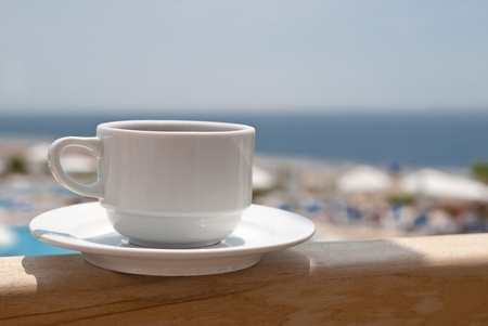 White cup of coffee near sea beach and pools