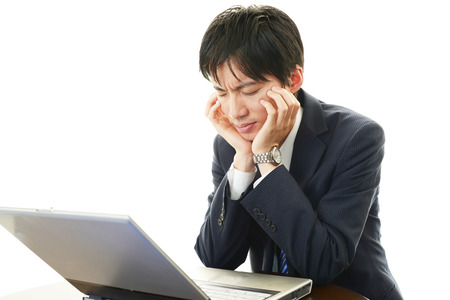 Stress Asian man looking at laptop