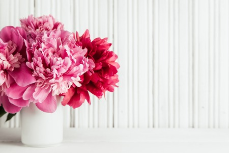 Photo for Fresh peonies flowers in white vase on white wooden background, copy space, selective focus - Royalty Free Image