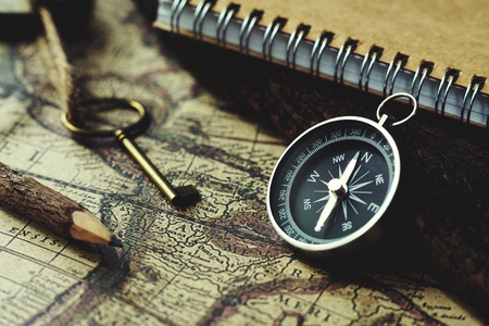 Foto de Compass, key, pencil and book on blur vintage map background, retro classic color tone - Imagen libre de derechos