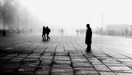 Silhouette of man taking a break in foggy morning