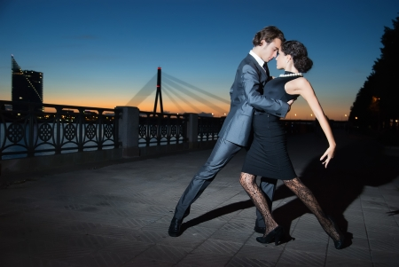 young couple dancing tango on the quay of the river city Riga, night