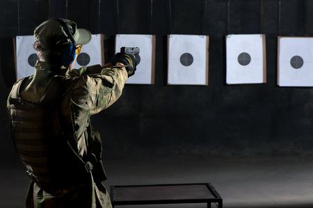 Photo pour Man shooting with gun at a target in shooting range - image libre de droit