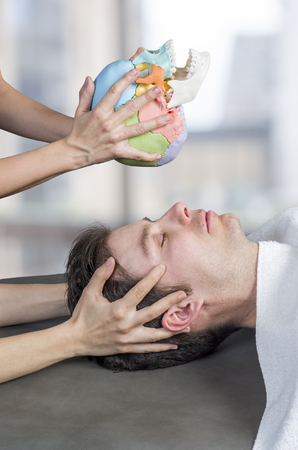 Physiotherapist doing a cranial sacral therapy to a man patient and another physiotherapist with a fake skull showing position of the hands.