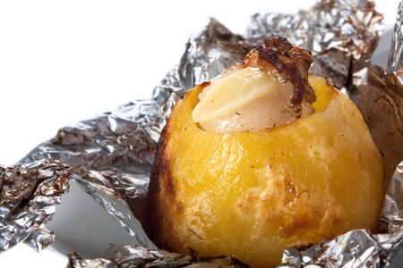 Baked potato in foil isolated on white background
