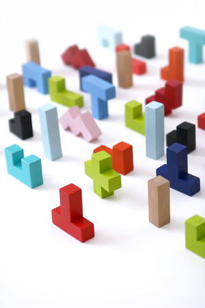Wooden colored 3D geometric shapes arranged chaotic on a
