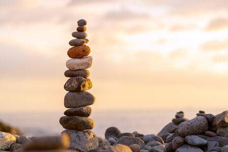 Photo pour Balanced stone pyramide on shore of the ocean at dawn. Sea pebbles tower closeup symbolizing stability, zen, harmony, balance. - image libre de droit