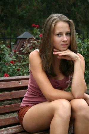 Foto de Pretty girl in rose garden seating on the bench - Imagen libre de derechos