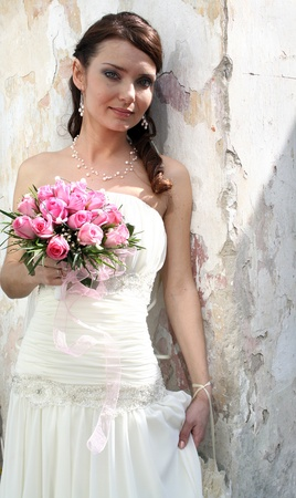 A lovely bride with bouquet from roses on background of wall.
