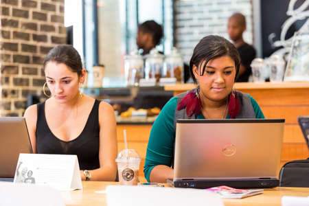 Photo pour Johannesburg, South Africa - October 03 2013: Diverse Female Customers using Internet in a Coffee Shop - image libre de droit