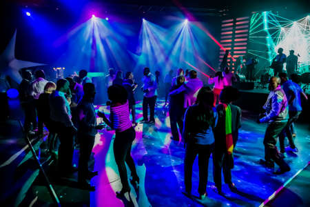 Photo pour Johannesburg, South Africa - April 13, 2016: Group of people dancing on a dance floor in dark night club environment - image libre de droit