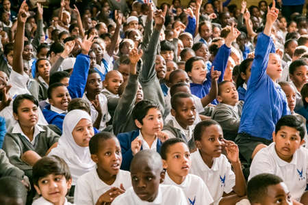 Photo pour Johannesburg, South Africa - September 10, 2015: Young diverse school children sitting on the floor at a morning assembly - image libre de droit