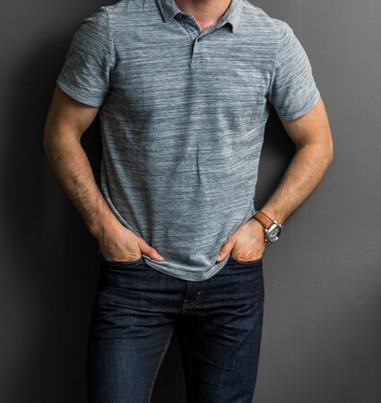 Photo pour Cropped Head young Man in casual collared grey shirt and jeans with hands in pockets - image libre de droit