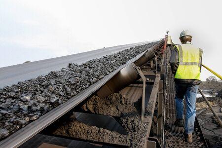 Photo pour Man walking up a platform with a conveyor belt with coal ore on - image libre de droit
