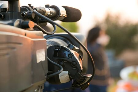 Photo for TV Camera and presenter host on a live news broadcast on location at sunrise - Royalty Free Image