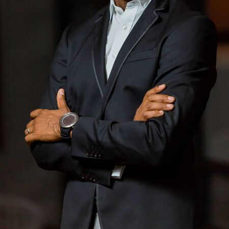 Photo pour Close-up cropped head of Arab Indian hands and arms of businessman in a suit with folded arms - image libre de droit