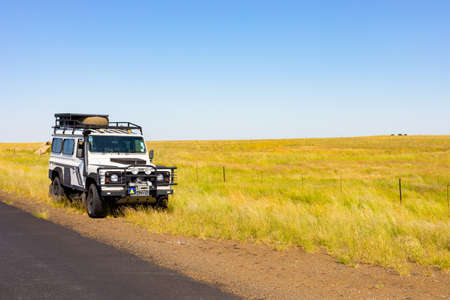 Photo for Karoo, South Africa - March 17 2019: Old Land Rover Defender parked beside a national highway in the countryside of South Africa - Royalty Free Image