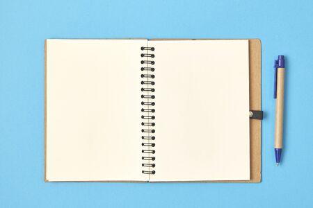 Photo pour Open white paper with pen on a blue background. Top view. - image libre de droit