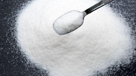 Photo pour Sugar falling from spoon on black background. - image libre de droit