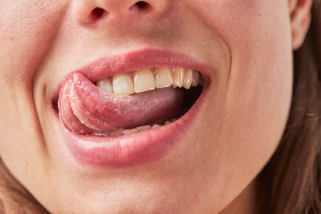 Photo pour Beautiful young woman leaking teeth with tongue close-up - image libre de droit