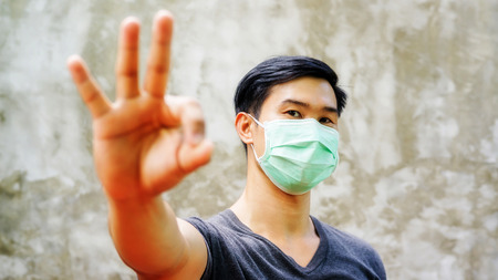 Photo for the man wears a protective mask and put his hand up for an OK symbol. - Royalty Free Image