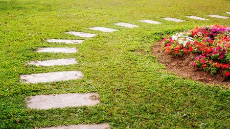 Foto de cement walkway in a flower garden. - Imagen libre de derechos