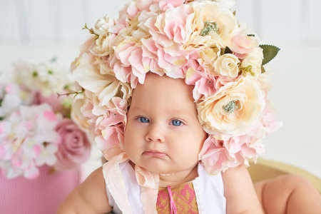 Photo pour Sweet funny baby in hat with flowers. Easter greeting card, copyspace for your text. Poster for Easter holiday. Congratulations on Mother's Day. Cute baby girl 6 months wearing flower hat - image libre de droit