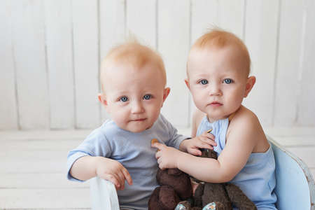 Foto de Children's Day. Sweet funny baby on bed in children room. Greeting card, copyspace for your text. Poster for spring and summer holiday. Congratulations on Mother's Day. Cute baby twin boys. - Imagen libre de derechos