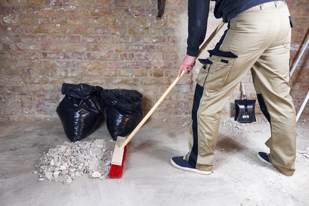 Photo pour Worker sweeping rubble and dust with broom - image libre de droit