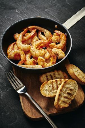 Foto de fresh delicious fried tiger prawns in a pan and toasts on wooden board - Imagen libre de derechos