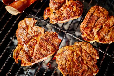 Photo pour Juicy beef steaks on hot grill with flame on barbecue in the garden - image libre de droit