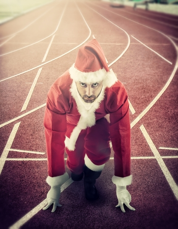 Santa Claus in the starting position on a running track.