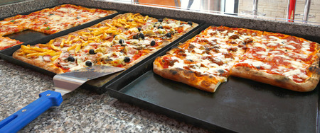 Counter of the pizzeria with trays and square pieces of pizza