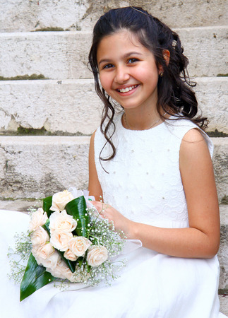 Smiling young girl in white dress for First Communion